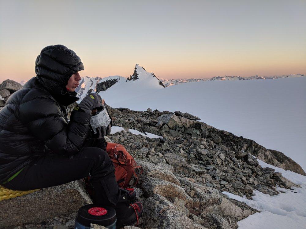 Jake, eating dinner with sunset over inspiration glacier